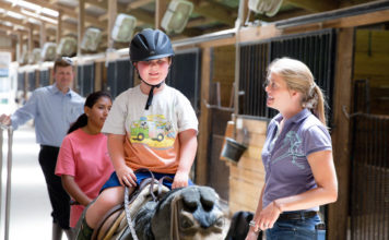 """Clients do a variety of exercises on a """"practice"""" horse before riding, such as getting on/off, holding the reins correctly, and doing leg exercises by posting."""